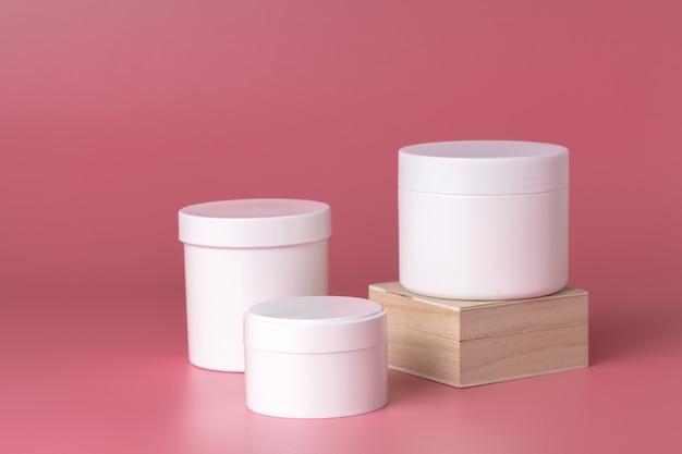 Confezione rotonda di crema. vaso di crema isolato sul rosa
