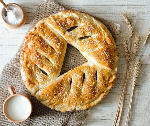 Torta rotonda su tela di sacco, latte, sale e spighe di grano e una tazza di latte su una superficie di legno chiaro