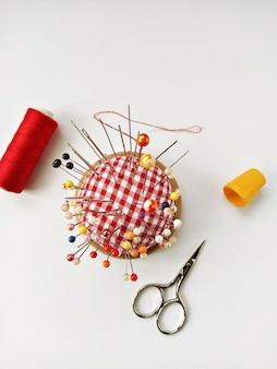 Puntaspilli rotondo con tanti spilli, ditale giallo, rocchetto di filo e forbici. accessori per il cucito distesi su sfondo bianco