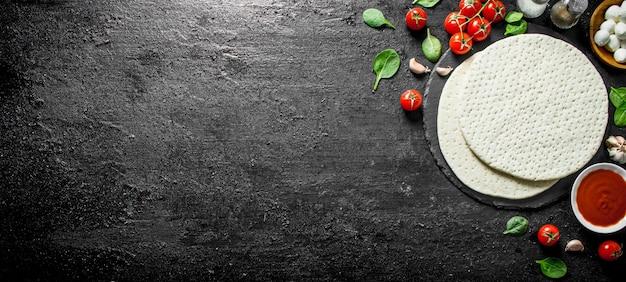 Pasta per pizza tonda con mozzarella, concentrato di pomodoro e spinaci. su sfondo nero rustico