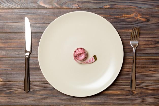 Piatto tondo con nastro di misura interno con forchetta e coltello. vista dall'alto del concetto di obesità