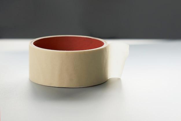 Rotolo rotondo del nastro adesivo bianco, nastro adesivo su una superficie con spazio di copia
