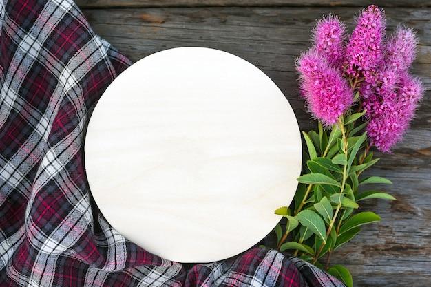 Segno rotondo carta bianca fiori rosa e tessuto a scacchi sul tavolo di legno