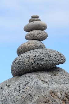 Pietre rotonde impilate piramide in riva al mare, concetto di equilibrio
