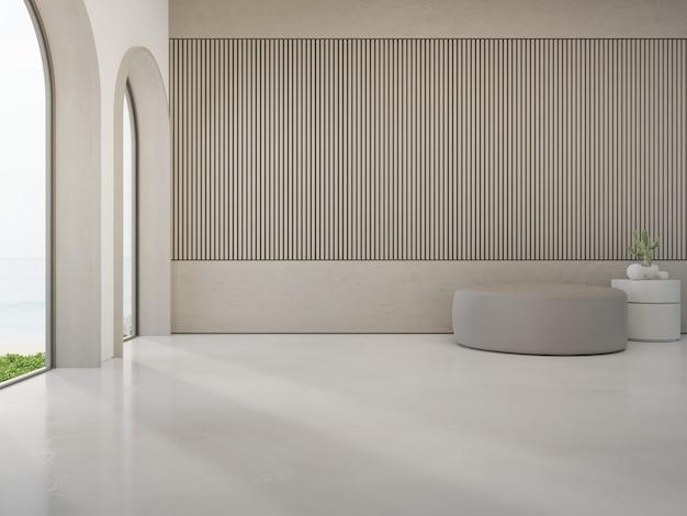 Sgabello rotondo sul pavimento di cemento bianco di un luminoso soggiorno in una moderna casa sulla spiaggia o in un hotel di lusso