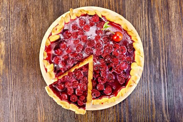 Torta dolce rotonda con ciliegie e gelatina su uno sfondo di assi di legno