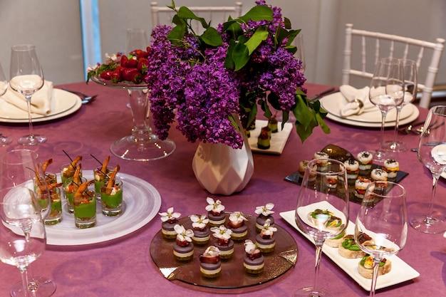 Tavola rotonda con tovaglia rosa e set di posate con stuzzichini per il banchetto. catering, tavoli server per bonquet