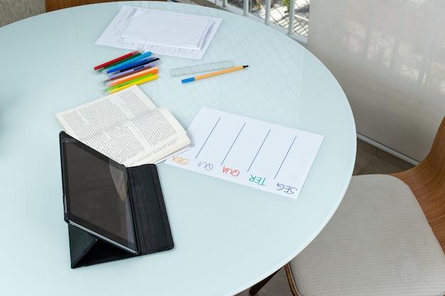 Tavola rotonda con oggetti di lavoro documenti aperti libro penne tablet.
