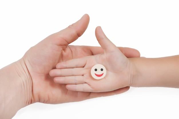 Un sorriso rotondo della compressa si trova sul palmo della mano di un bambino che si trova sul palmo della mano di un uomo su uno sfondo bianco vista dall'alto