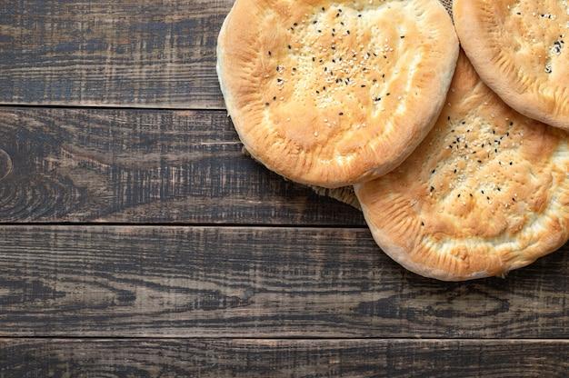 Tortillas azzime rotonde su un fondo di legno. pane al sesamo semplice e rustico. vista dall'alto, distesi, copia spazio.
