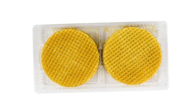 Wafer rotondi con crema al caramello in un contenitore di plastica isolato su uno sfondo bianco. torte fresche fatte in casa. disposizione piatta.