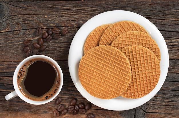 Cialde rotonde con caramello in piatto e tazza di caffè caldo su tavolo di legno scuro, vista dall'alto