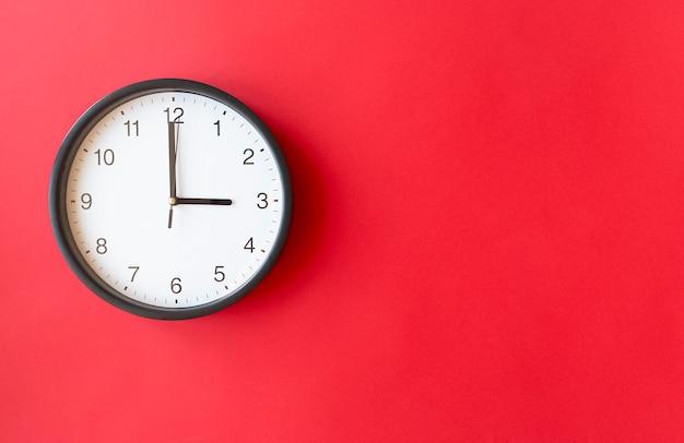 Orologio da parete rotondo sulla superficie rossa che mostra le 3 in punto, layout, vista dall'alto, posto per il testo