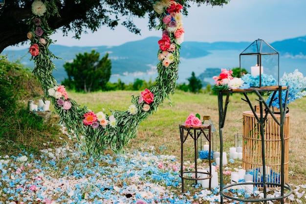 Arco nuziale rotondo di fiori e rami di ulivo appesi al