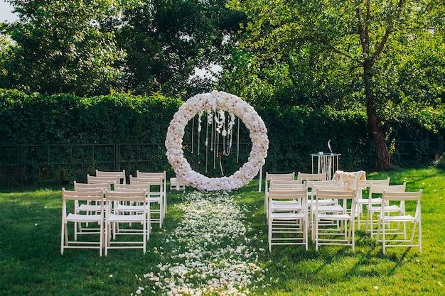 Arco nuziale rotondo fatto di fiori bianchi con perline e piume su uno sfondo di verde accanto a sedie di legno bianco
