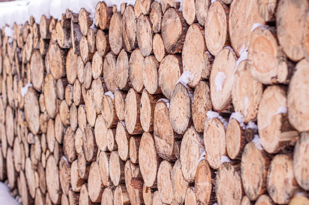 La legna tonda, spolverata di neve, si trova in file diritte sulla strada, predisposta per riscaldare la stufa in inverno. texture di legno rotondo.