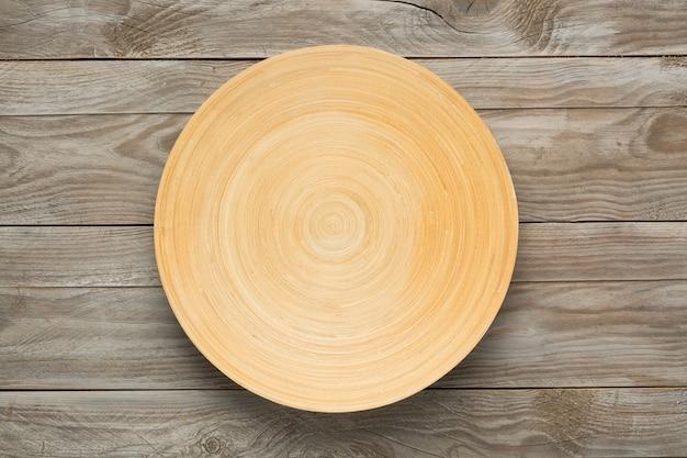 Piatto di legno rotondo sulla tavola di legno. vista dall'alto. mockup per il progetto alimentare.
