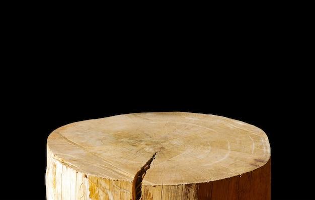 Sega rotonda in legno tagliata a forma di cilindro per l'esposizione del prodotto isolato su sfondo scuro