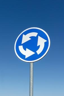 Segnale stradale dell'incrocio della rotonda contro il cielo blu blue
