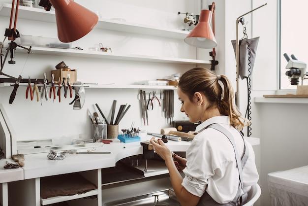 Normale amministrazione. vista posteriore del giovane gioielliere femminile seduto nel suo laboratorio di gioielleria e che tiene in mano strumenti di gioielleria per il lavoro. affare. laboratorio di gioielli. attrezzature per gioielleria