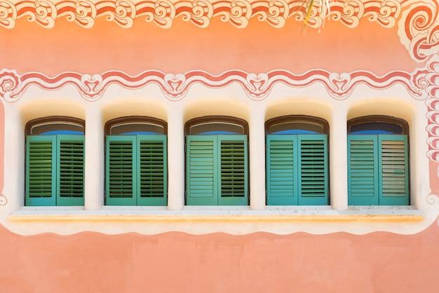 Fila di finestre verdi d'arte al muro di casa rosa. park guell di antonio gaudi a barcellona