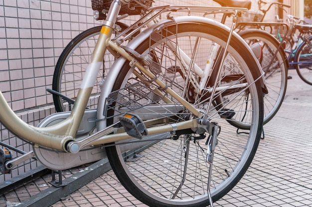 Fila di biciclette in stile giapponese classico con sedili al parcheggio sul marciapiede a tokyo, giappone