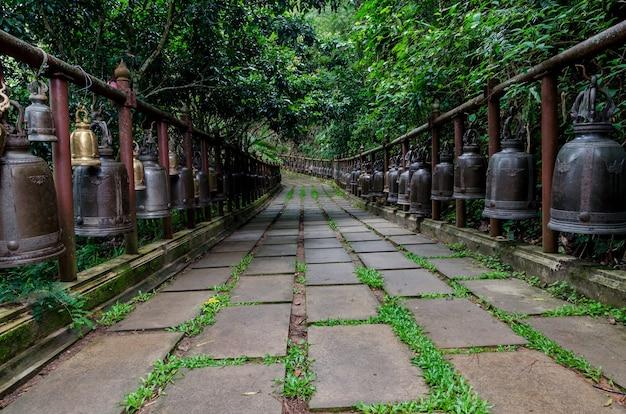 Fila di grande campana in ottone nel tempio thailandese, giorno di pioggia, thailandia