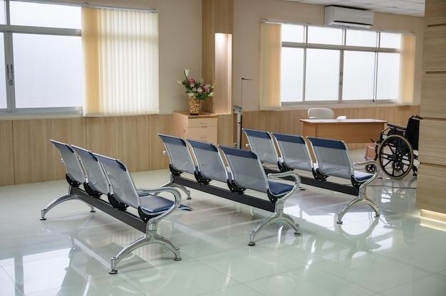 Fila di sedie vuote blu e sedia a rotelle in sala d'attesa in ospedale