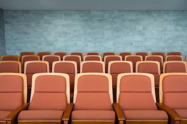 Fila di sedili teatrali marroni e pareti di marmo nella sala dell'auditorium