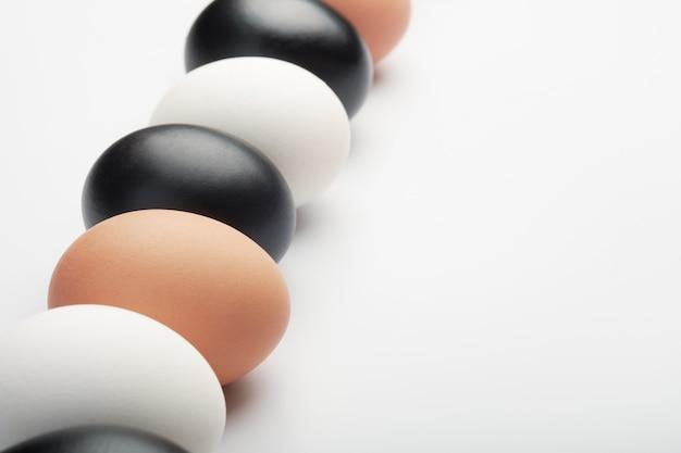 Fila di uova di diversi colori su sfondo bianco. uova di gallina nere, bianche e marroni.