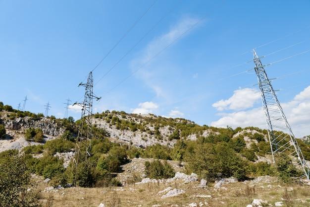 Fila di linee elettriche in montagna tra la foresta