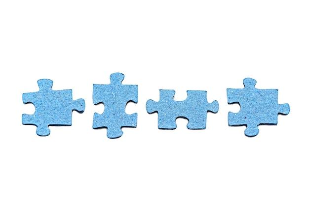 Una fila di quattro pezzi di puzzle blu scollegati isolati su bianco