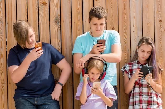 Fila di quattro amici che utilizzano telefoni cellulari. concetto di bambini e gadget.