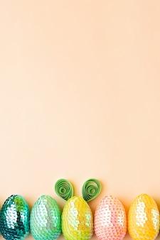 Fila di uova multicolori sullo sfondo pastelloun uovo con orecchie di conigliominimo concetto di pasqua