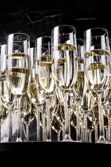 Una fila di bicchieri pieni di champagne sono allineati pronti per essere serviti. bicchieri di champagne di lusso su una parete nera