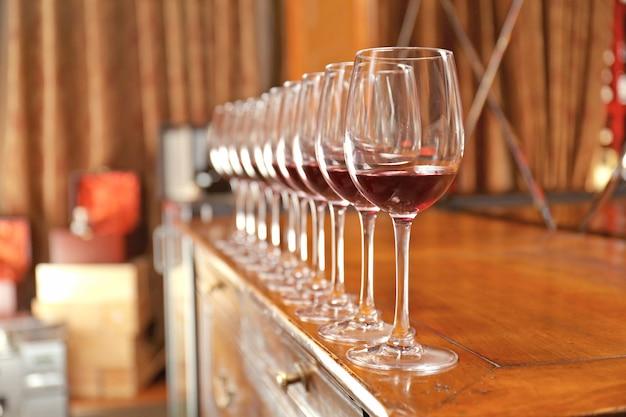 Fila di bicchieri con vino rosso sul bancone del bar