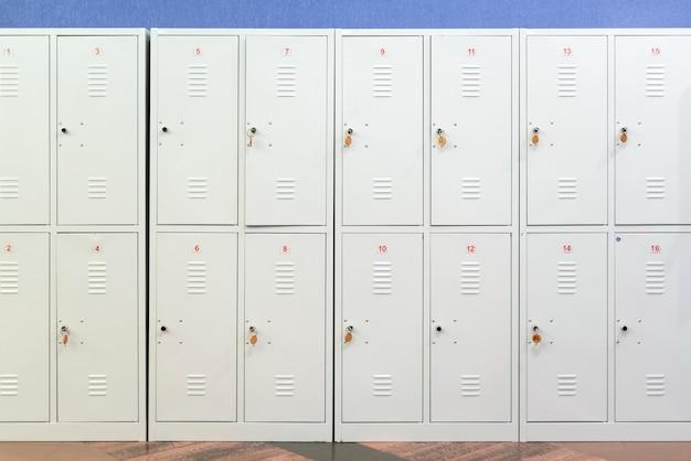 Una fila di armadietti scolastici in metallo grigio con le chiavi nelle porte.