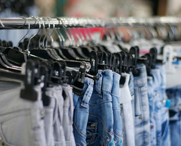 Fila di blue jeans impiccate in un negozio