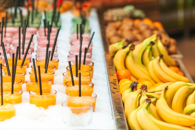 Fila di frullati sani di frutta e verdura fresca con ingredienti assortiti