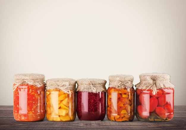 Fila di home conserve di verdure estive, vasetti di vetro su white