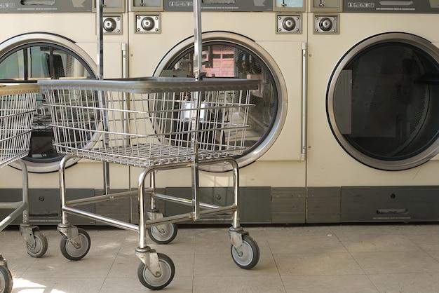 Fila di lavatrici industriali in lavanderia a gettoni.