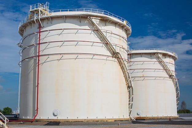 Fila di grandi serbatoi bianchi per olio di benzina