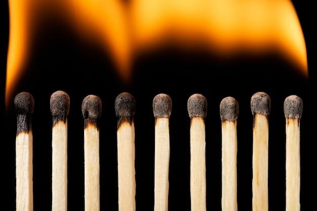 Fila di fiammiferi accesi su sfondo nero