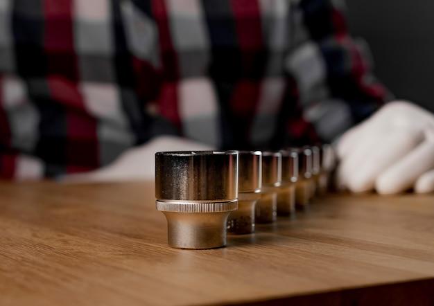 Fila di prese esagonali in acciaio metallico o teste metalliche esagonali sulla scrivania in legno. concetto di strumento di riparazione.