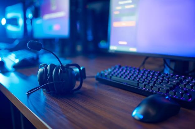 Fila di monitor, tastiere e cuffie, interno del club di gioco, nessuno