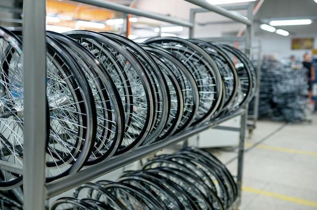 Fila di nuove ruote di bicicletta in alluminio sullo scaffale, nessuno. negozio di parti di biciclette in fabbrica, pneumatici in hangar, catena di montaggio, cerchi per biciclette con mozzi e raggi