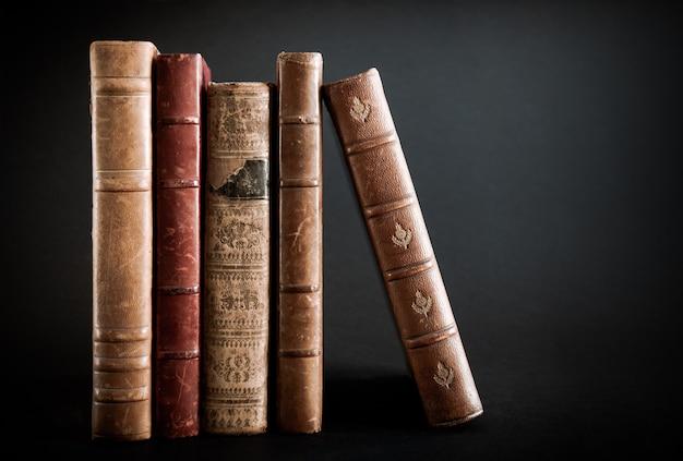 Fila di vecchi libri isolati su sfondo nero