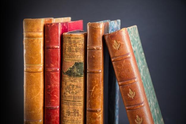 Fila di vecchi libri isolati su sfondo scuro