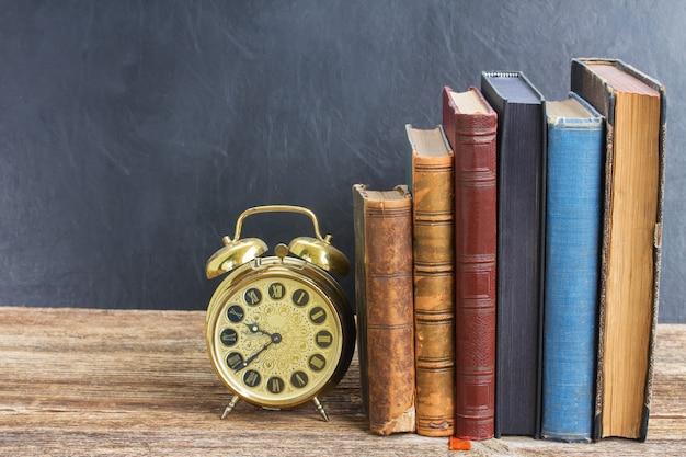 Fila di vecchi libri con sveglia antica sullo scaffale di legno