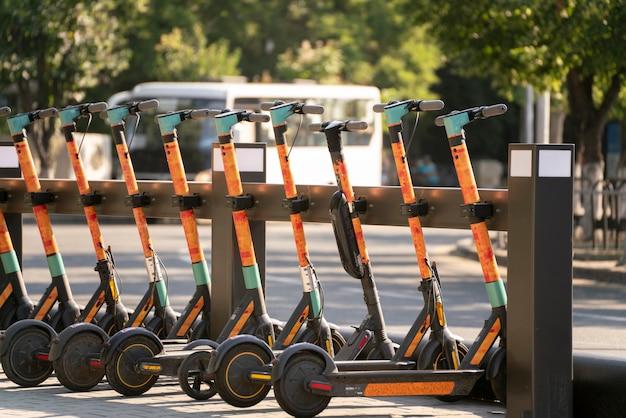 Una fila di scooter parcheggiati sul marciapiede della città, veicolo elettrico